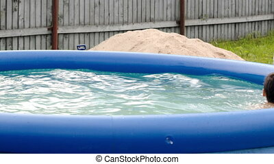 Boy swimming in inflatable pool in the yard - Dolly shot of...