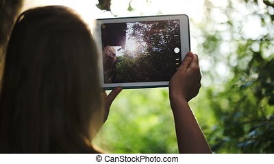 Woman taking pictures of nature with a tablet computer