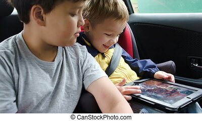 Boys with tablet computer during traveling by car