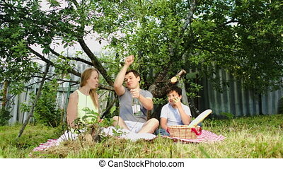 Parents with their son having picnic in the courtyard -...