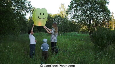 Mother with two sons flying smiling fire lantern