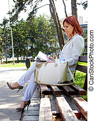 girl reading a magazine in the park