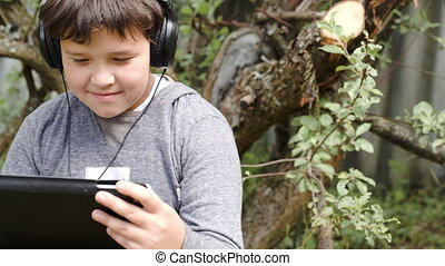 Boy in headphones with touchpad outdoor - Dolly shot of a...