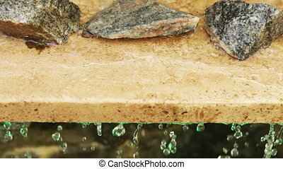Granite slab with stones and water - Drops of water flowing...