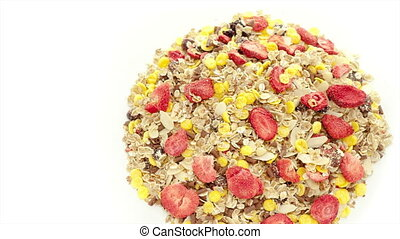 Mixed muesli rotating on the white table with white seamless...