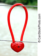Metal padlock in the form of heart on fence, symbol of love