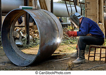 Welder in the mask and uniform is welding steel tubes.