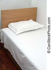 white bedroom with a single bed and pillow