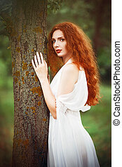 Beautiful redhead woman wearing white dress stands near tree...