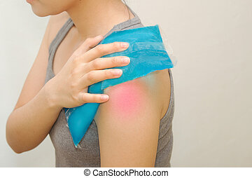 woman applying cold pack on swollen hurting shoulder