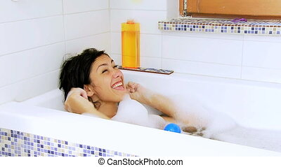 Woman in bath tub playing - Happy funny raining balls in...