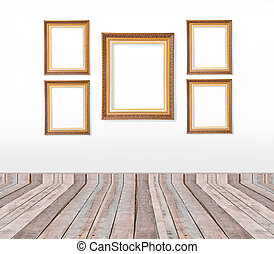 Set of gold vintage picture frames on the wall inside the...