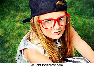 red spectacles - Modern girl teenager sitting on a grass.