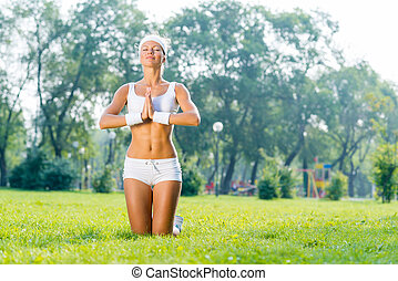 Yoga practice - Young sport woman in park practicing yoga