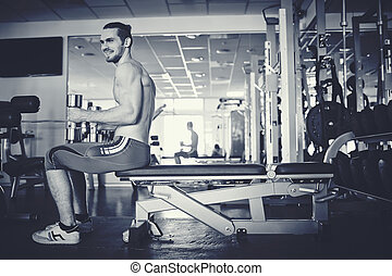 Man training in gym - Young man with barbells sitting in gym