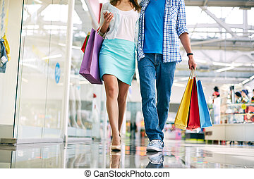 Shoppers walking - Legs of young couple going in the mall