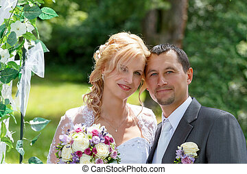 beautiful young wedding couple in park, blonde bride and her...