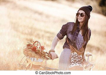 Young pretty brunette woman posing on the nature with bike in summer sunshine. Fashion portrait.