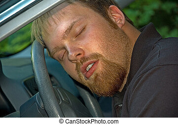 Young Man Asleep At Steering Wheel of Car - This young...