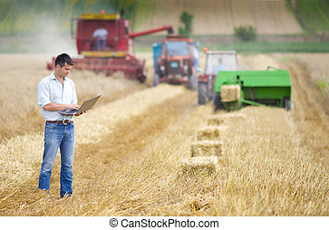 Harvesting - Young landowner with laptop supervising...