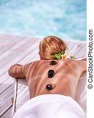 Hot stone massage on luxury spa resort on the beach, young...