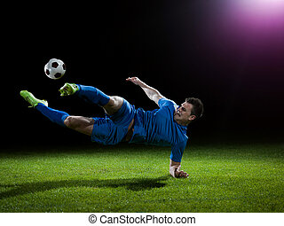 soccer player doing kick with ball on football stadium field...