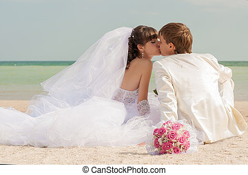 Young and beautiful bride and groom on the beach in summer