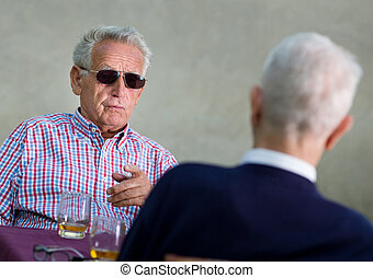 Discussion - Old man with black sunglasses pointing...