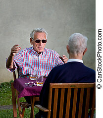 Discussion - Old man with black sunglasses explaining...