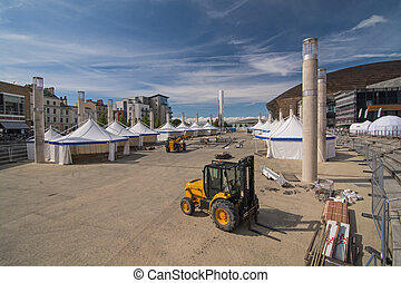 Setting up a Public Event - Workmen setting up static tents,...
