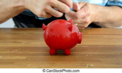 filling money pig - saving money in red money box pig