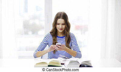 smiling student girl with smartphone and books - education,...