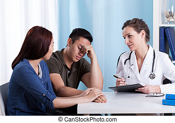 Female doctor talking with her patients - Female Caucasian...