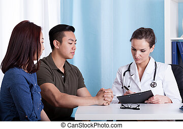 Asian couple during visit at doctors office, horizontal