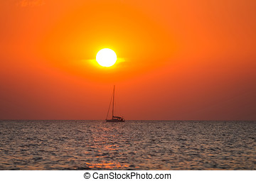 Boat sailing at sunset on open sea
