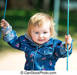 girl in swin - happy little baby on swing outside