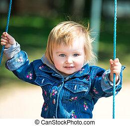girl in swin - happy little baby on swing outside