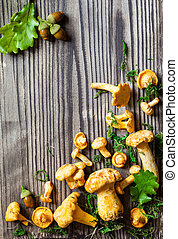 Mushrooms - Fresh mushrooms with moss and leaves on wooden...