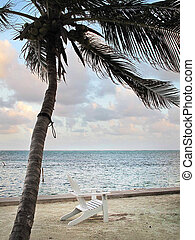White Chair on the Beach - A white lounge chair sits in the...