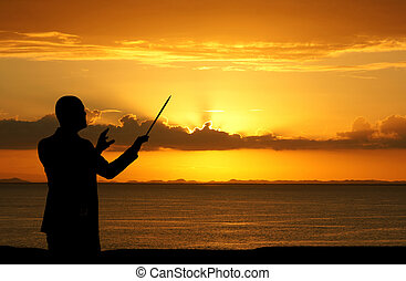 Conductor - Man conducting people during a sunset at the...