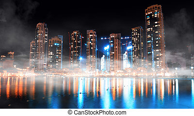 Dubai downtown night scene with city lights and fog