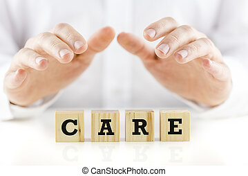 Care on wooden cubes with protective hands - The word - Care...
