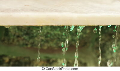 Granite slab with water - Drops of water flowing down from...