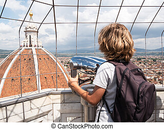 Boy looking through a sightseeing binoculars the Dome of...