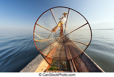 Burma Myanmar Inle lake fisherman on boat catching fish by...
