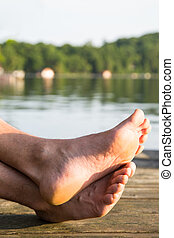 Happy feet - A mans feet comfortably rest on the dock at the...