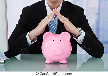 Businessman Protecting Piggy Bank At Desk - Midsection of...