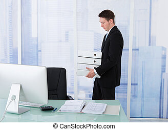 Businessman Carrying Stacked Binders At Desk - Side view of...