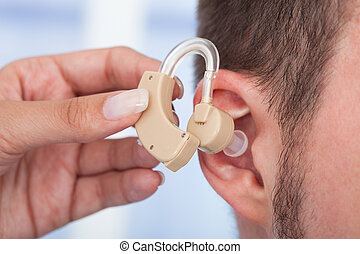 Doctor Inserting Hearing Aid In Mans Ear - Cropped image of...