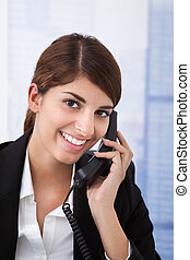 Businesswoman Using Landline Phone In Office - Portrait of...